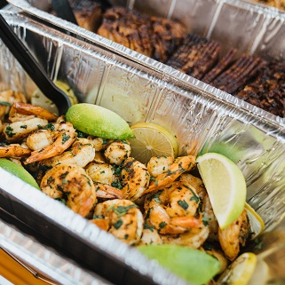 Shrimp with lime wedges and brisket.