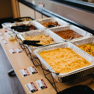Catering setup with mac and cheese with corn, chicken, and beef.