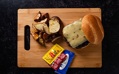 Burger on wooden board with condiments on side.