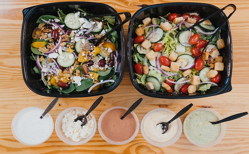 Two salads with dressings in front.