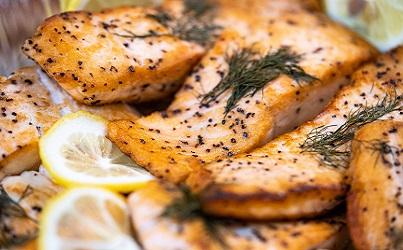 Salmon with lemons and garnish on top.