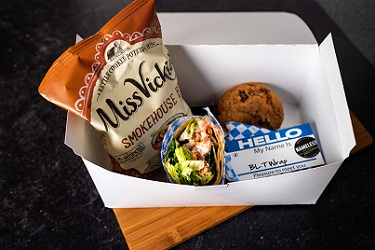 Boxed lunch with wrap inside, cookie, and chips.